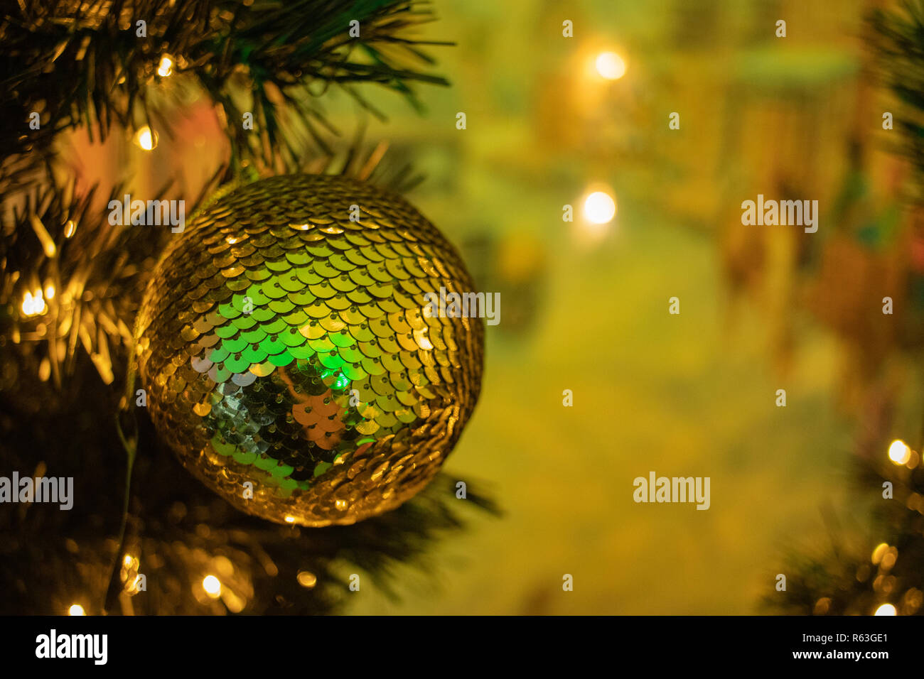 Golden Bauble On A Christmas Tree With Christmas Lights In The