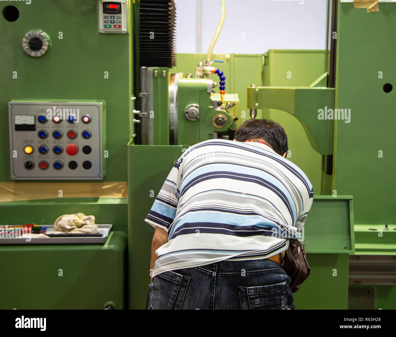 Worker operate CNC machine in factory, industrial machining - Stock Image