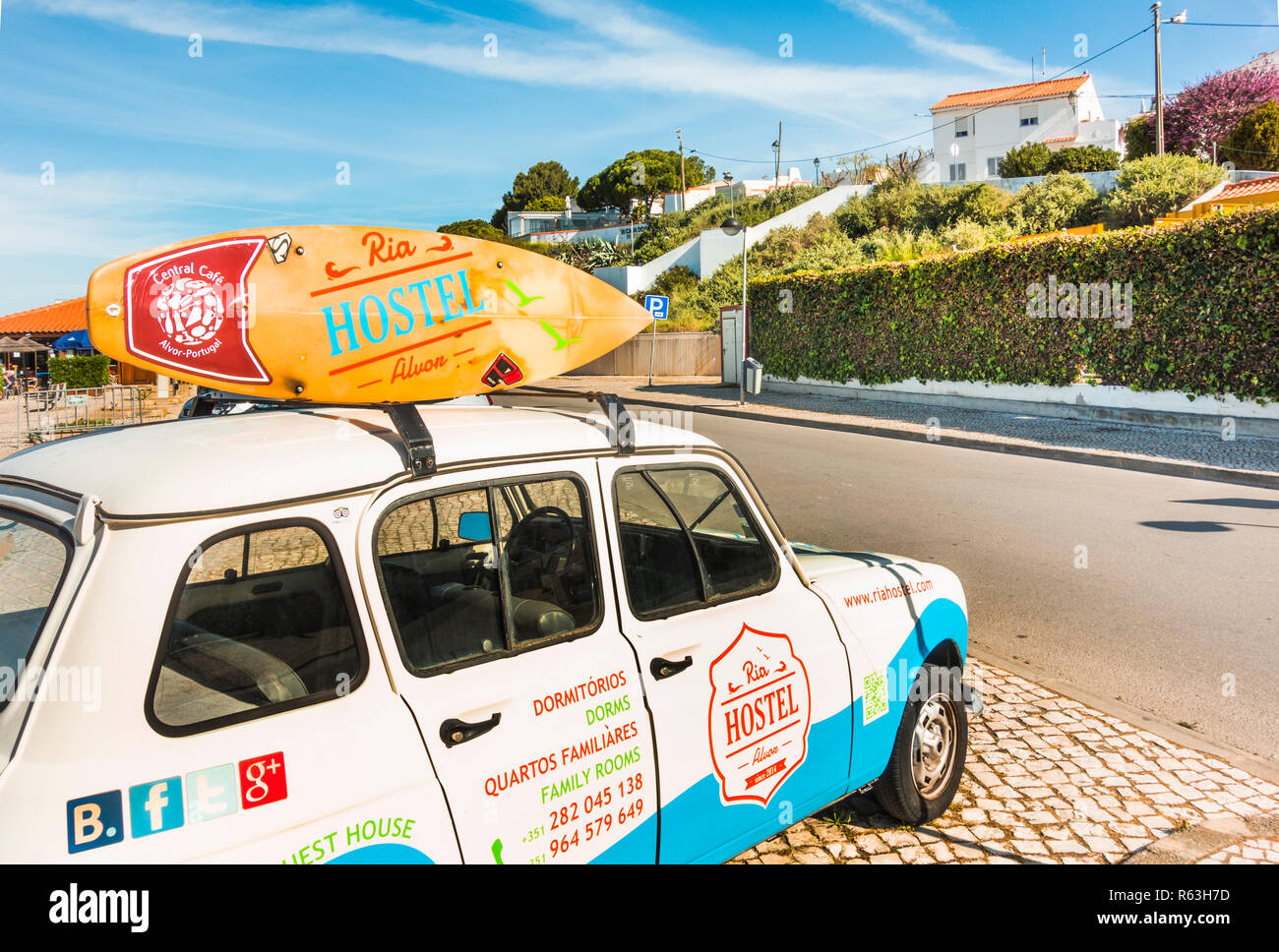 car with surfboard on the roof used as advertisement vehicle for ria hostel - Stock Image