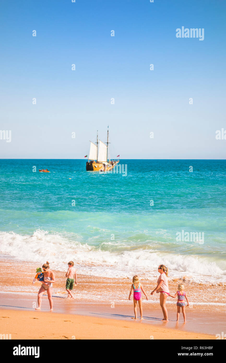 families at benagil beach with coast tour masted vessel in background - Stock Image