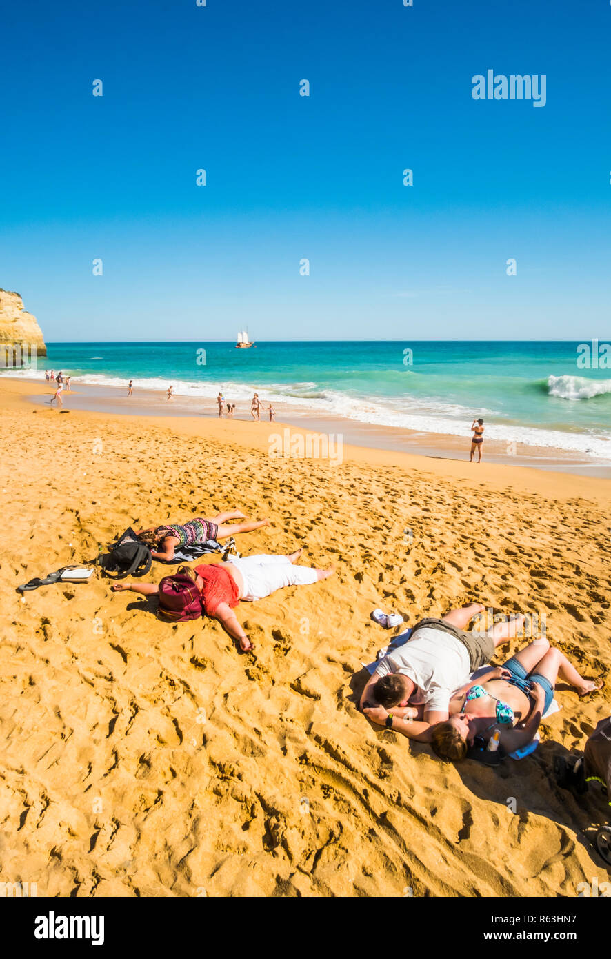 exhausted tourists at benagil beach with coast tour masted vessel in background - Stock Image