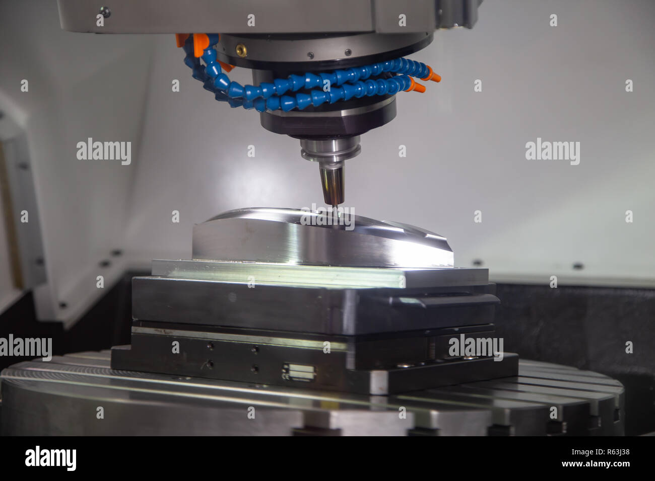CNC milling machine cutting workpiece, industrial machining - Stock Image