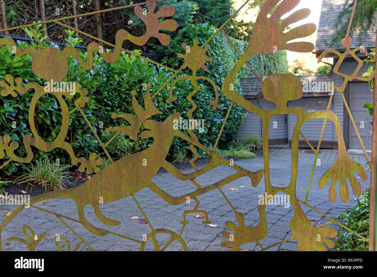 Close-up of whimsical cutout figures decorating the metal gate of a driveway - Stock Image