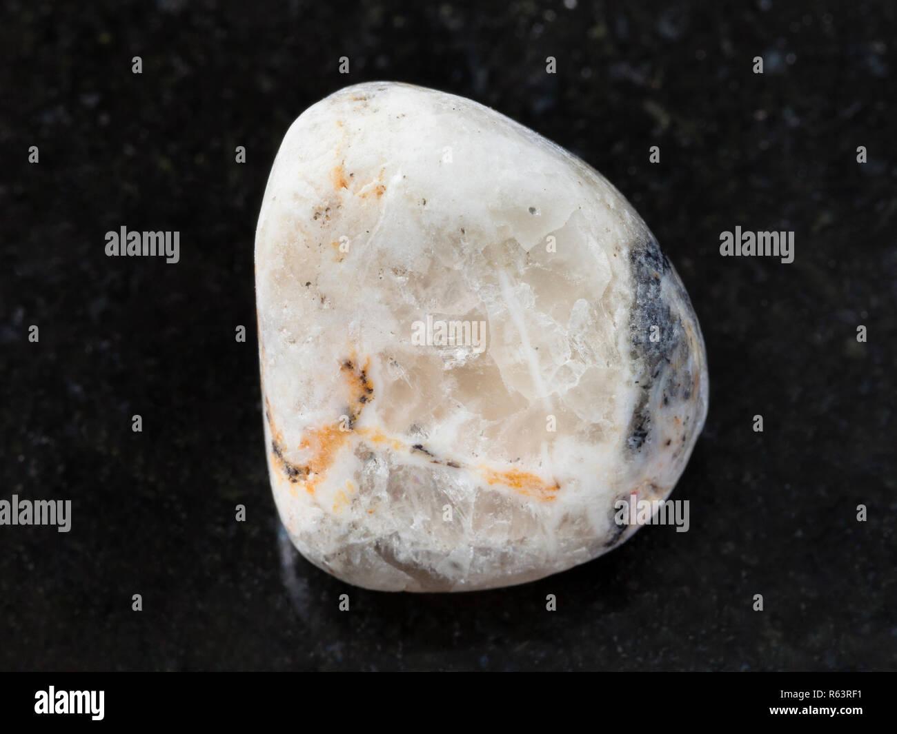 tumbled baryte stone on dark background - Stock Image