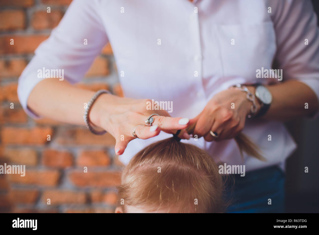 hands mom braid pigtails daughter - Stock Image