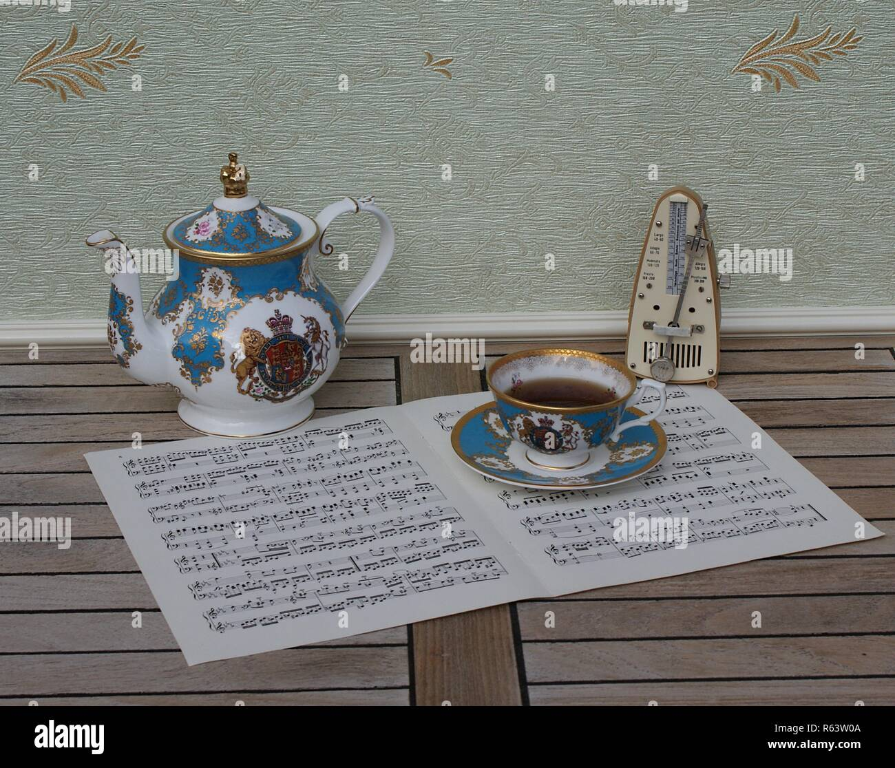 English teacup with saucer and teapot, fine bone china porcelain, and a metronome for music on a sheet of music - Stock Image