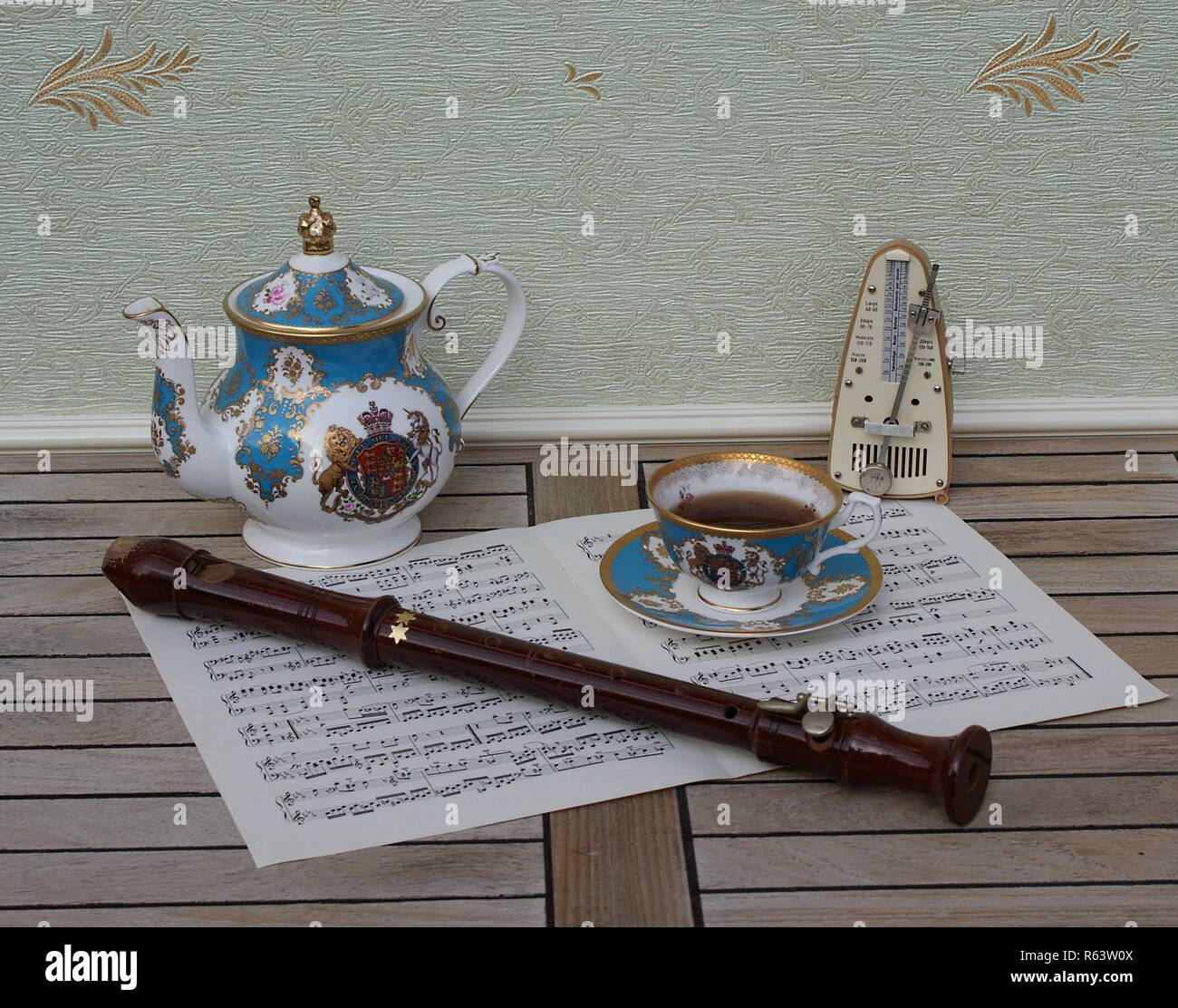 English teacup with saucer and teapot, fine bone china porcelain, metronome for music and a block flute on a sheet of music - Stock Image