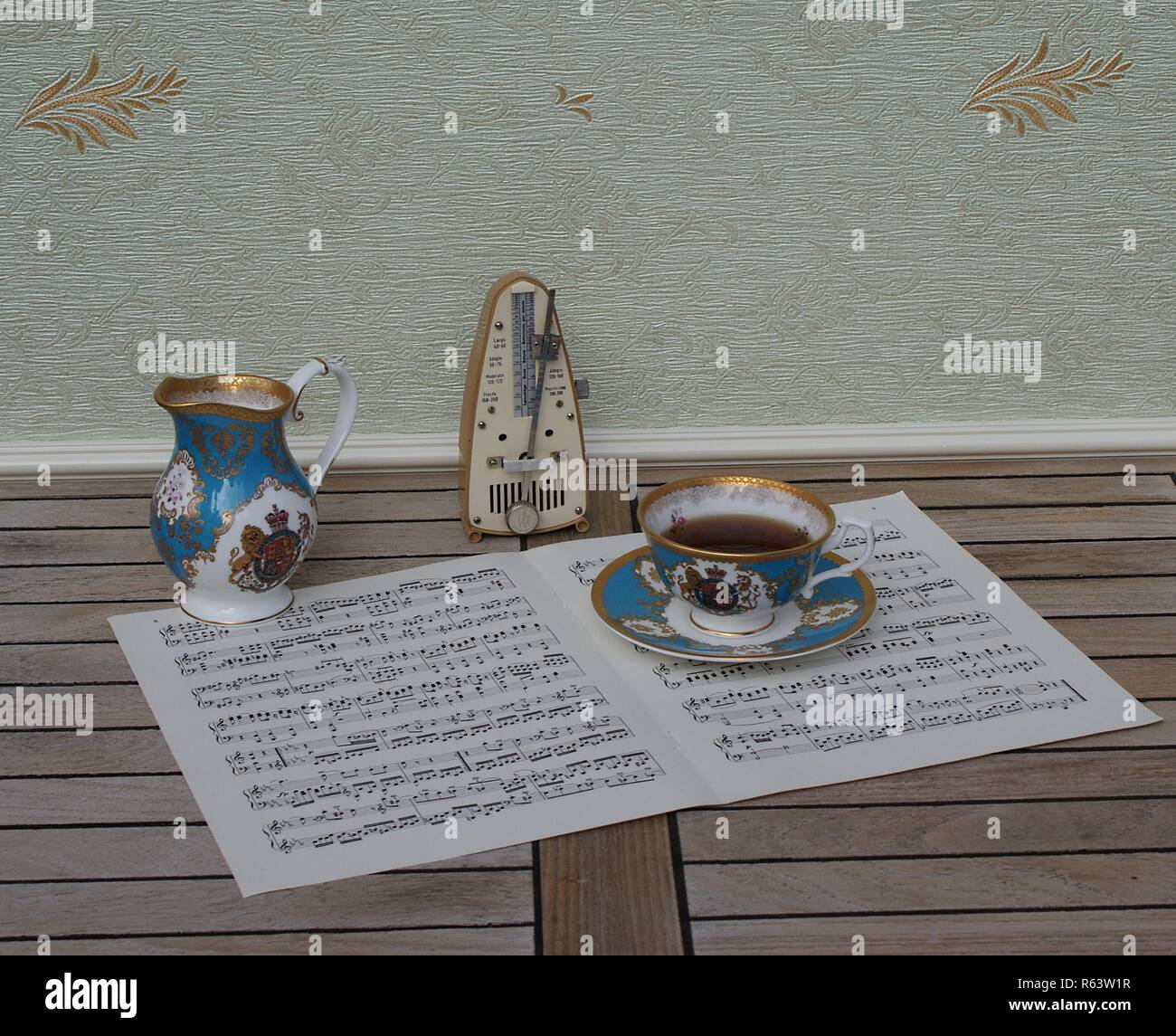 English teacup with saucer, cream jug, fine bone china porcelain, and a metronome for music on a sheet of music - Stock Image