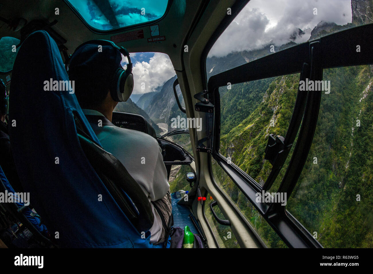 A helicopter flies along the Gori Ganga river towards the Milam Glacier in Pithoragarh District, Uttarakhand in northern India. - Stock Image