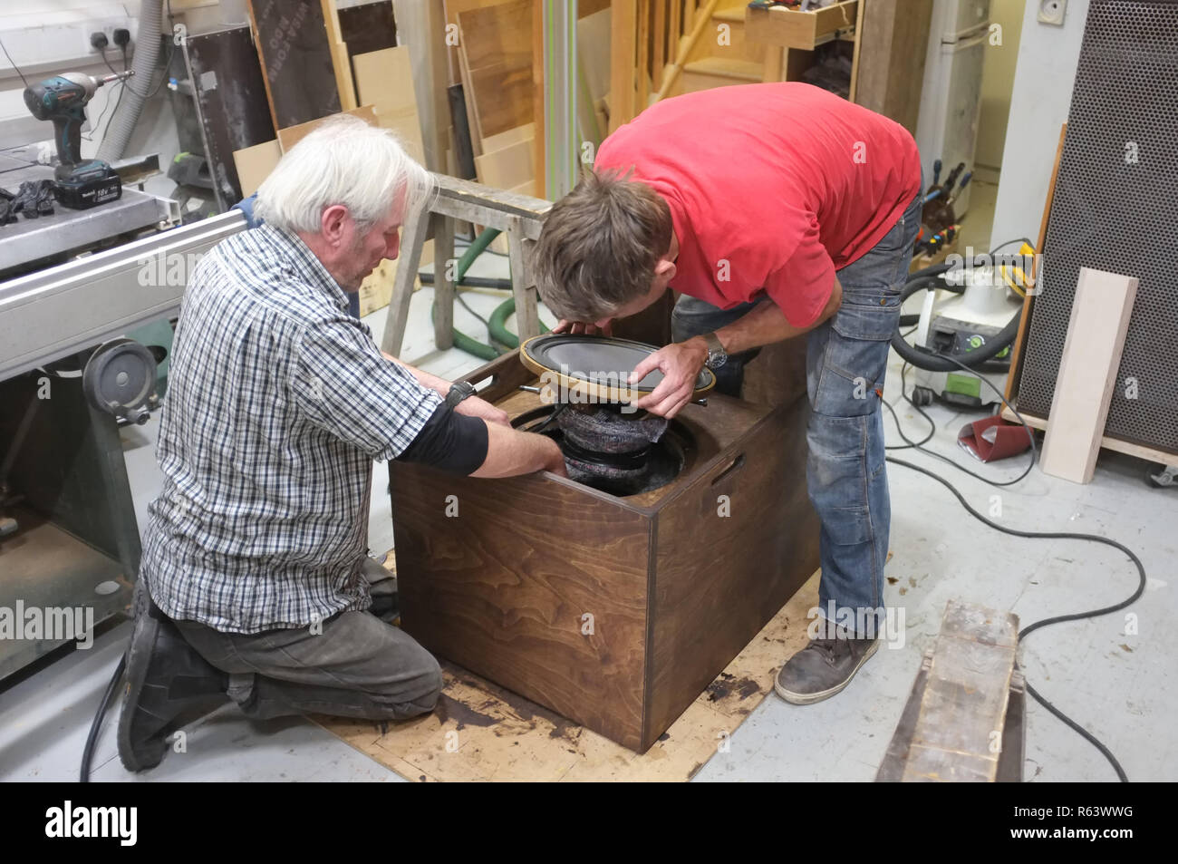 Two carpenters building a speaker for a sound system. Here Inserting a driver. - Stock Image