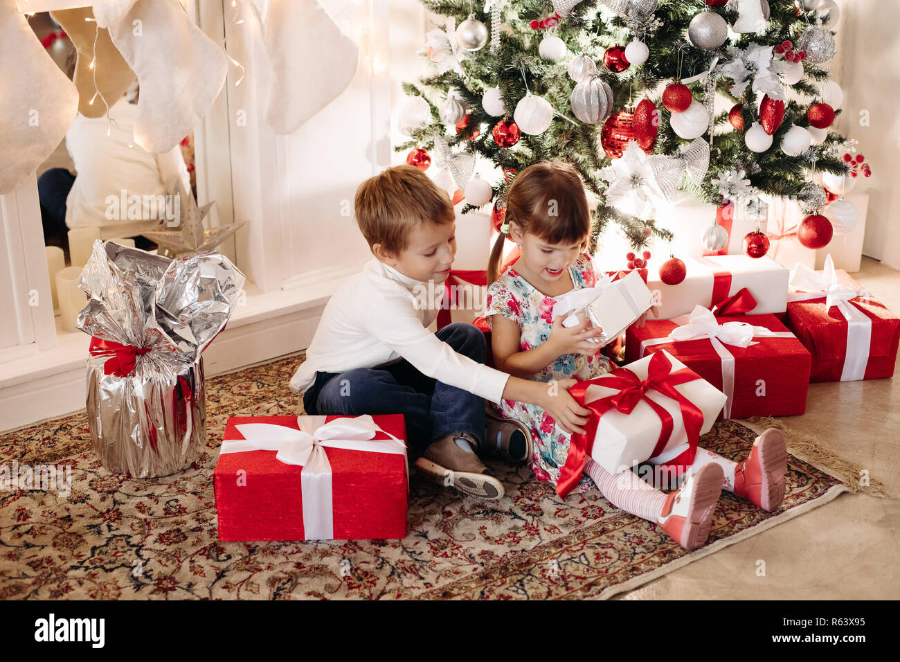 Brother in deer Christmas hat kissing his younger sister in head Stock Photo