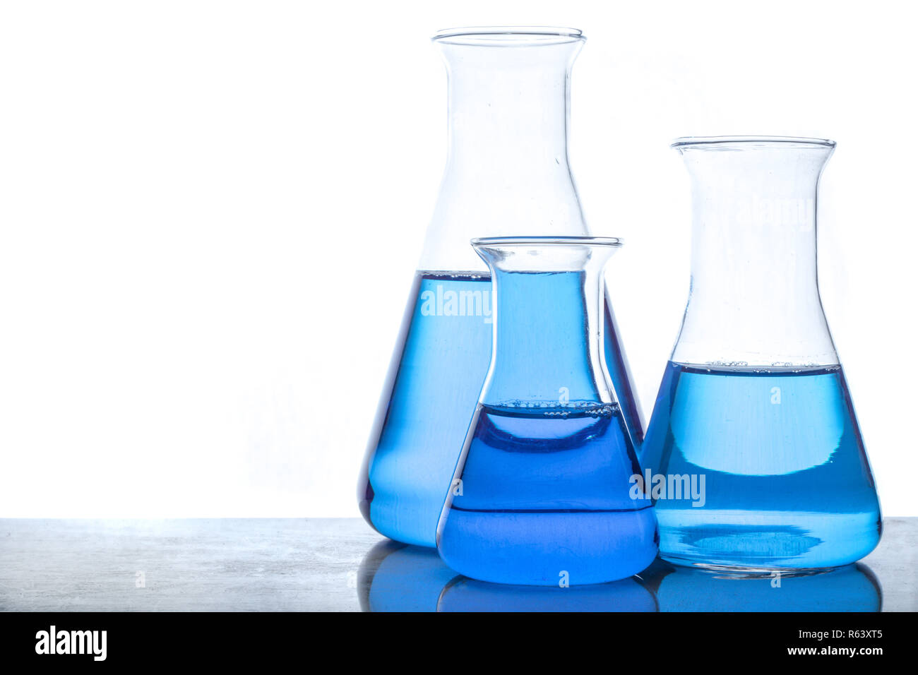 Glass flasks with blue fluid in used in chemistry experiments Stock