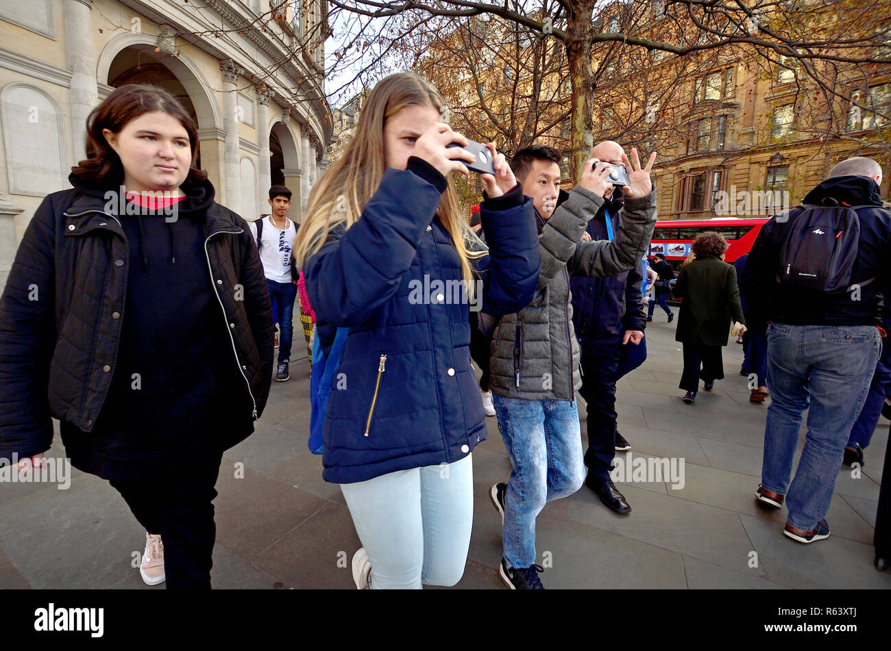 Young tourists filming on their mobile phone whie walking, Trafalgar Square, London, England, UK. - Stock Image