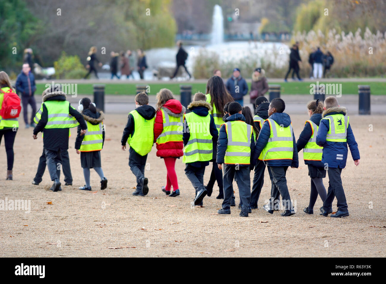 Primary school children in hi vis vests on a school trip in Horse Guards Parade, central London, England, UK. - Stock Image
