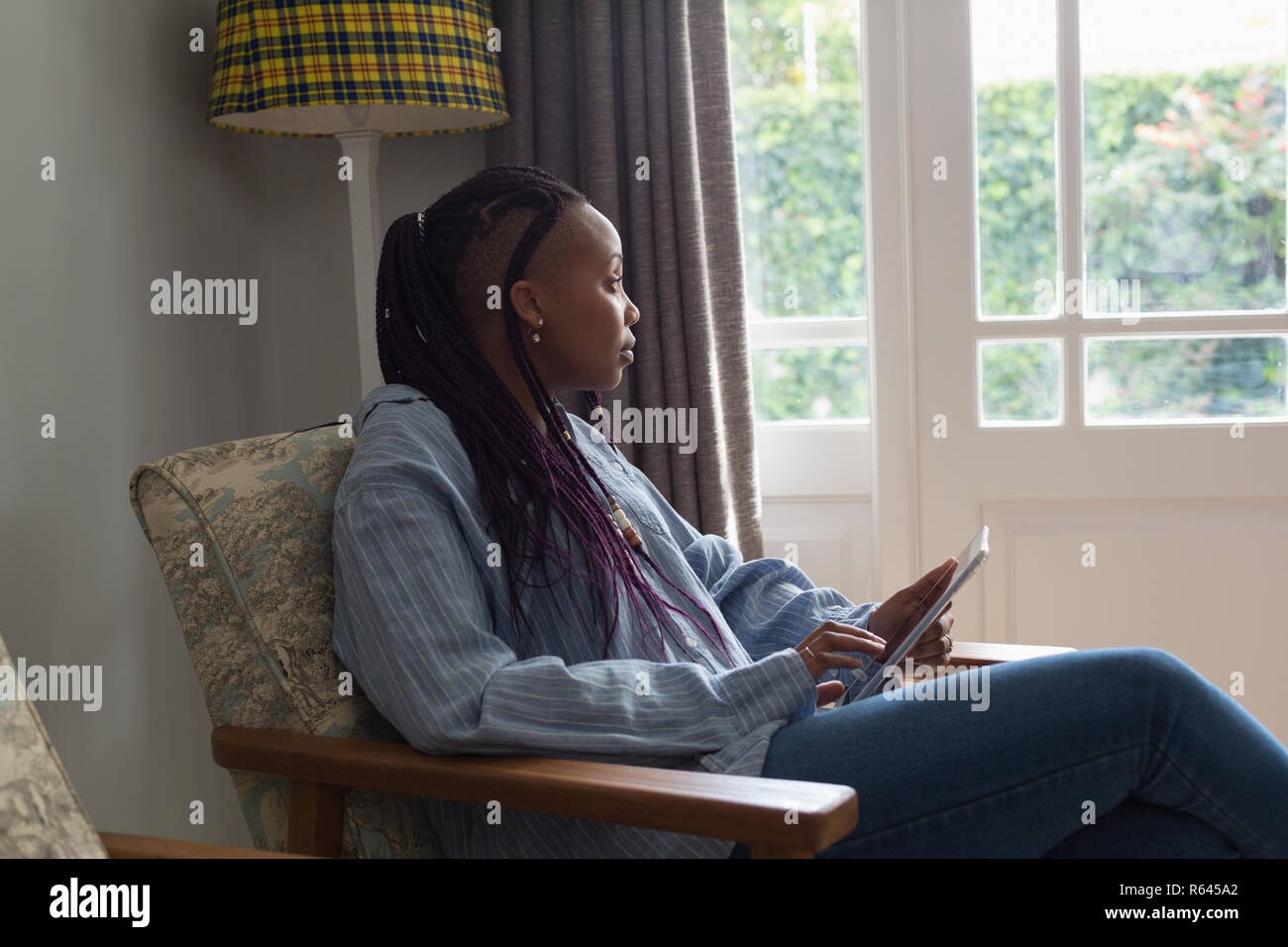 Thoughtful woman using digital tablet in a liviing room Stock Photo