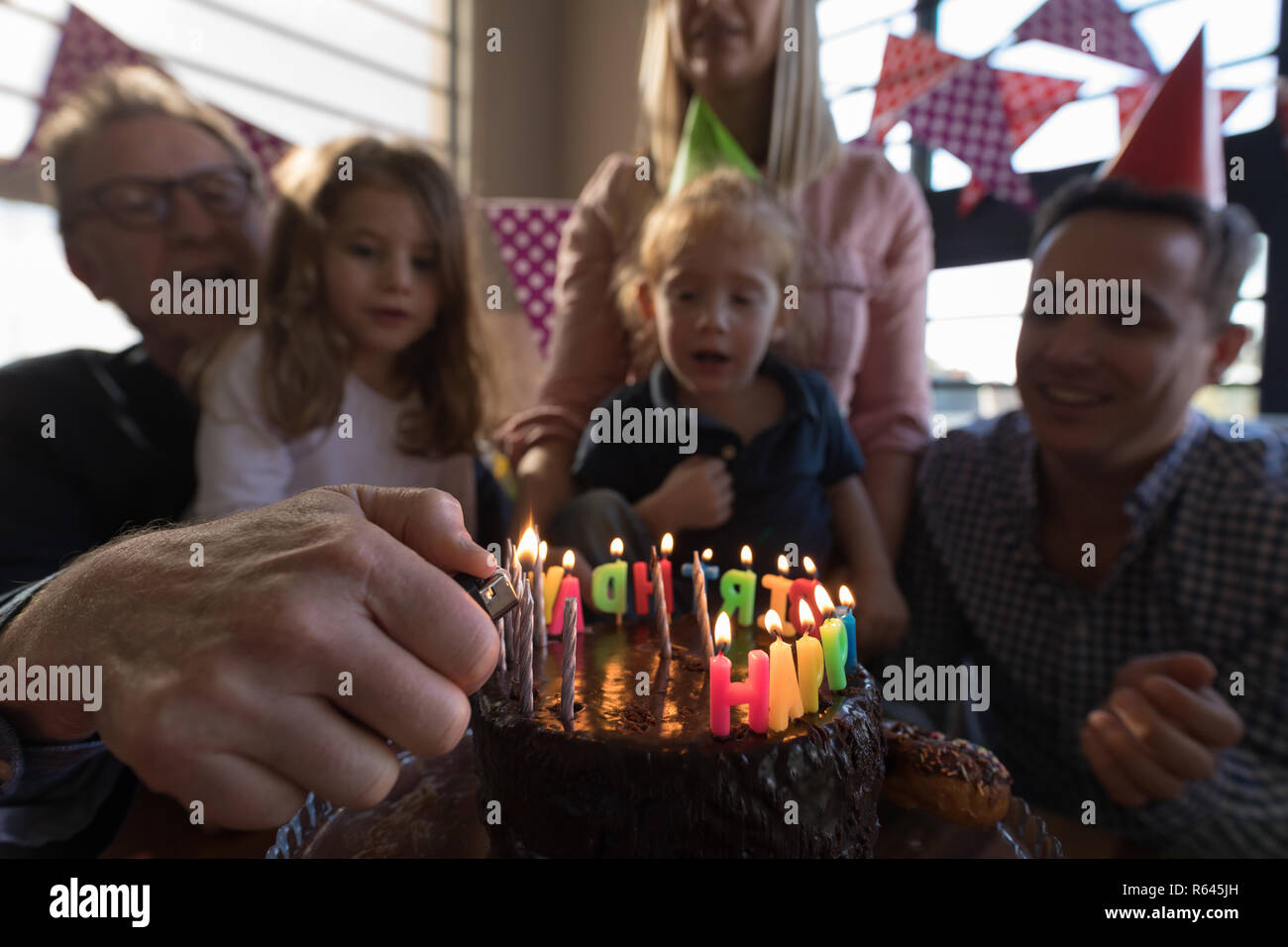 Multi-generation family celebrating birthday in living room Stock Photo