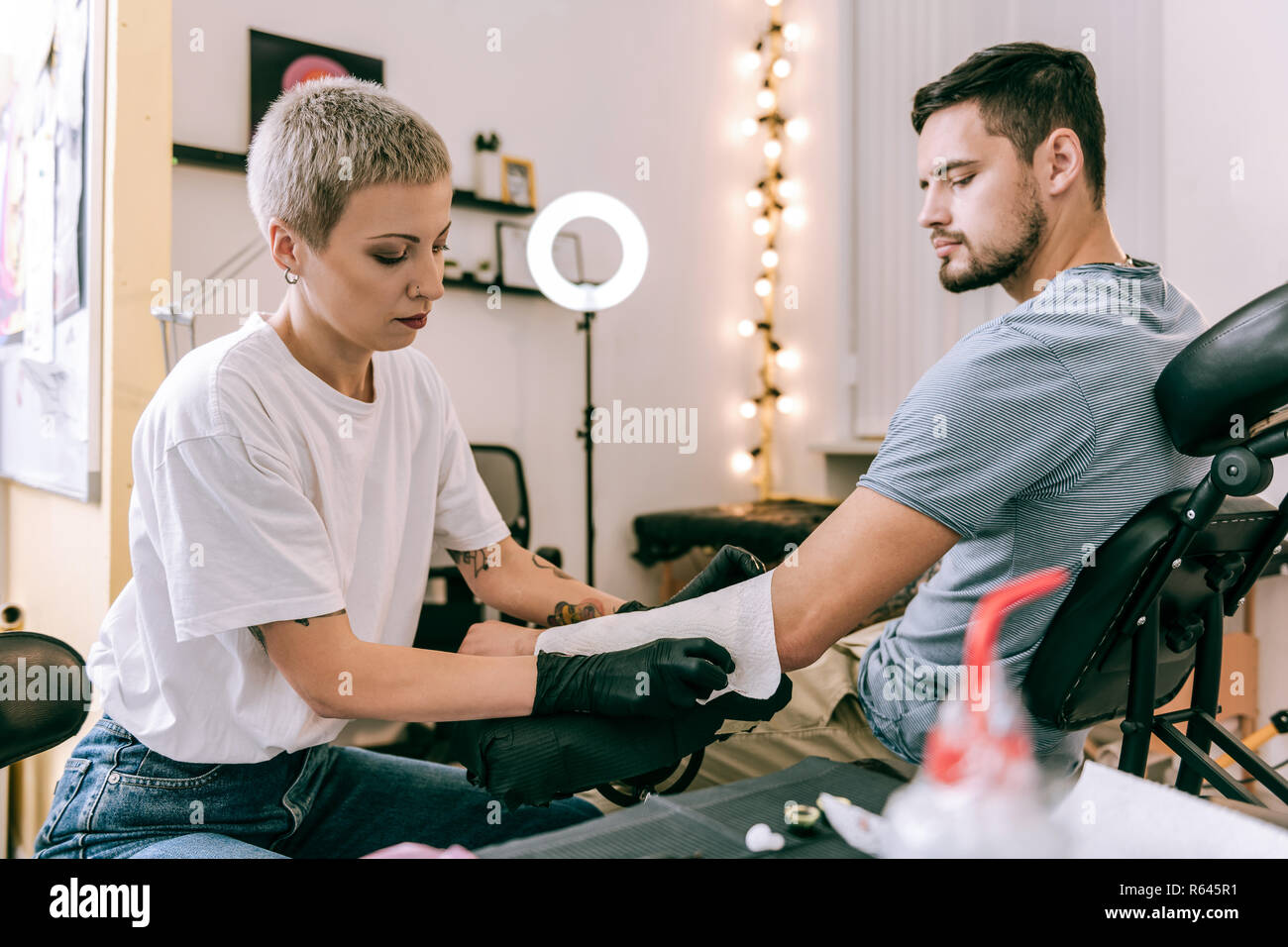 Attentive concentrated tattoo master using paper towel for absorbing - Stock Image