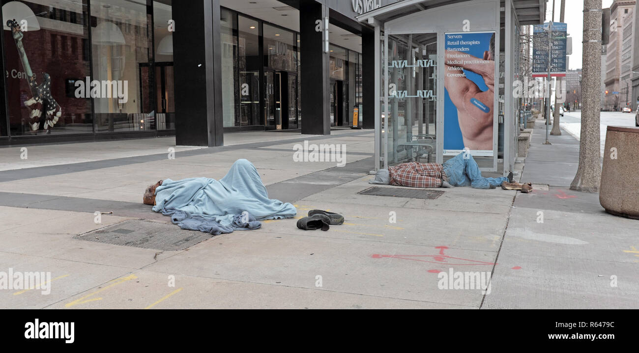 Two men sleep on the sidewalk at East 12th and Superior Avenue in downtown Cleveland, Ohio during the 2018 winter. - Stock Image