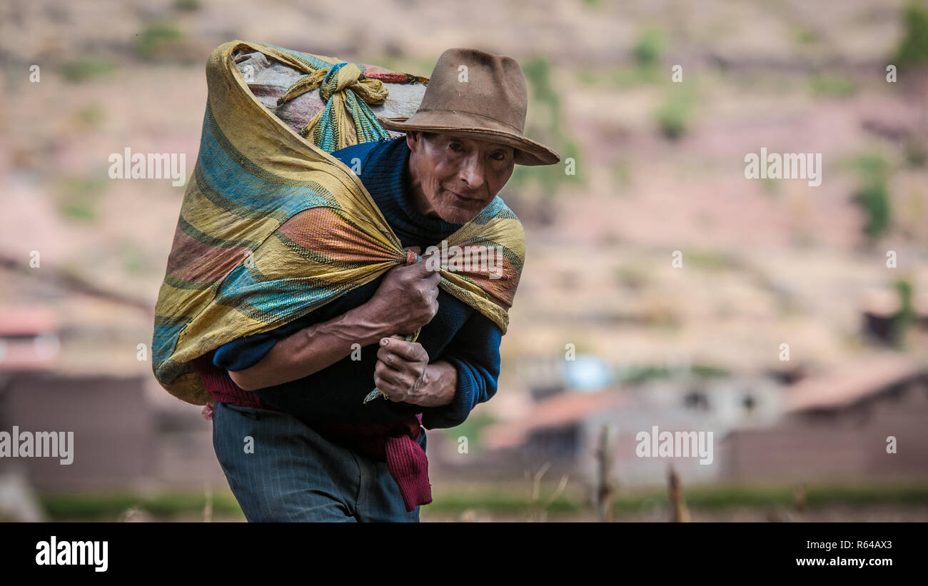 Pisac Peru August 12 2011 An Old Man Carrying A Heavy Bag Of Cereals Stock Photo Alamy