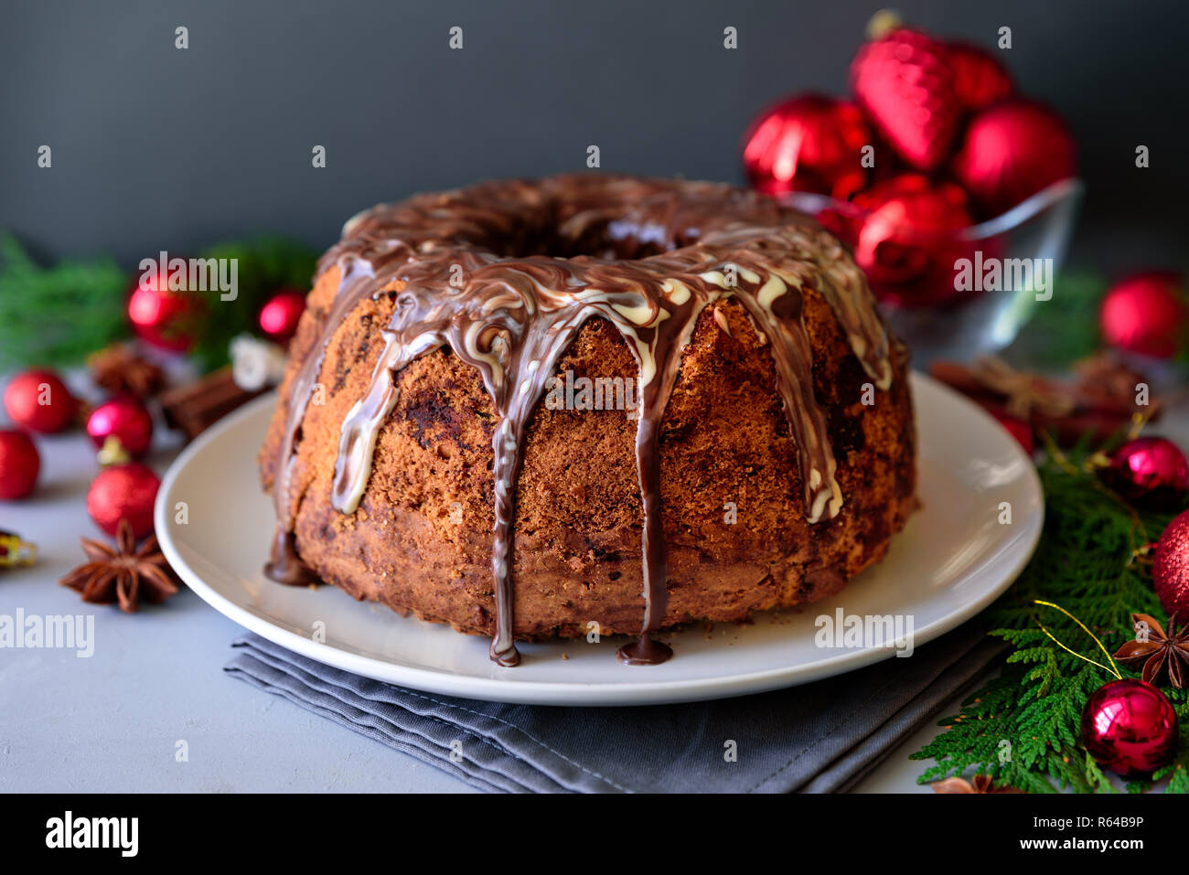 Christmas cake with chocolate icing on gray wooden background. Holiday decorations concept - Stock Image
