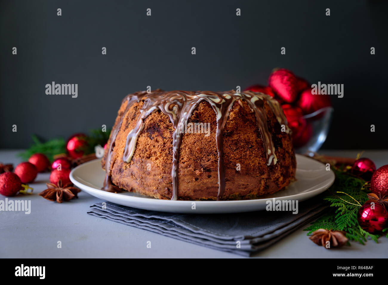 Christmas cake with chocolate icing on gray wooden background. Holiday decorations concept. Top view. Flat lay. Copy space - Stock Image