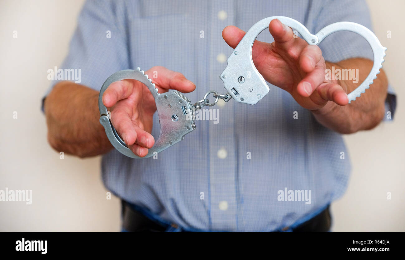 The man holds the handcuffs in his outstretched hand. Close up. Stock Photo