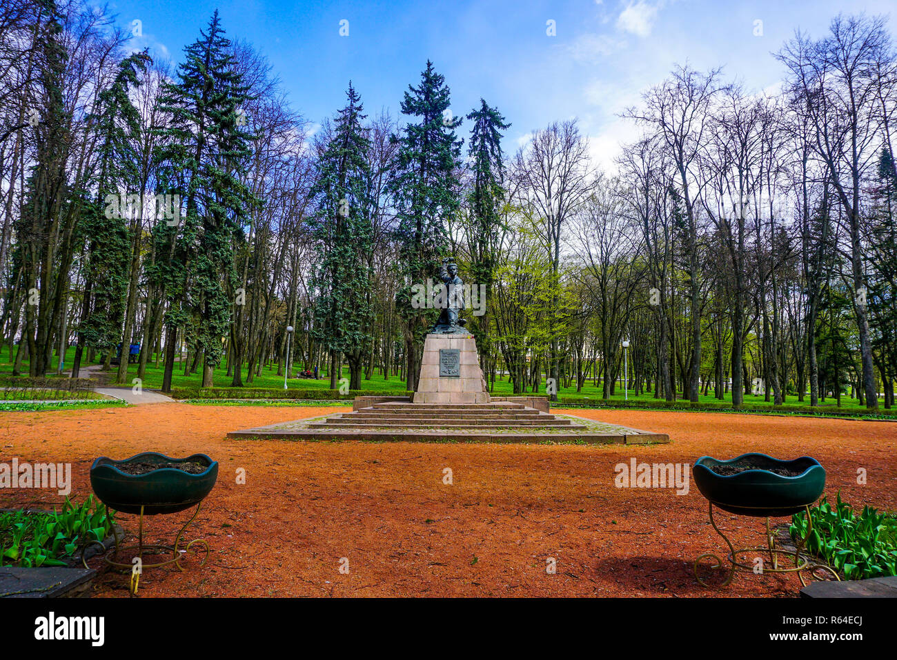 Minsk Marat Kazei Monument at Park with Trees and Cloudy Blue Sky Background - Stock Image