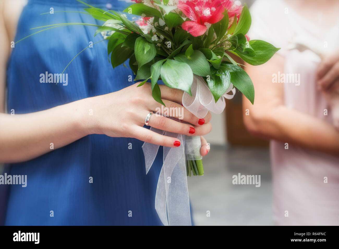 Close up of a bride's hands holding a wedding bouquet - Stock Image