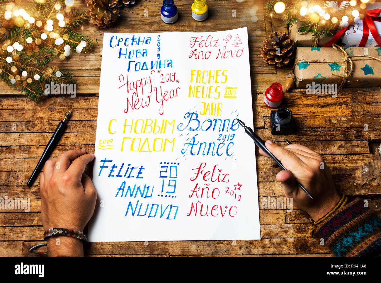Person writing a Happy new year card in various languages - Stock Image