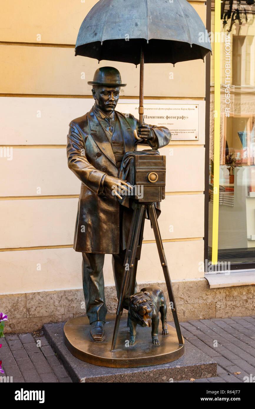 The famous bronze statue of photographer Karl Bulla in Malaya Sadovaya Ulitsa, St Petersburg, Russia. Plate camera, umbrella, and bowler hat. - Stock Image