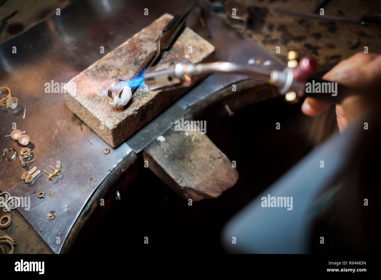 Jeweler soldering on work bench a gold ring with flame from welding torch in an authentic jewelry workshop - Stock Image