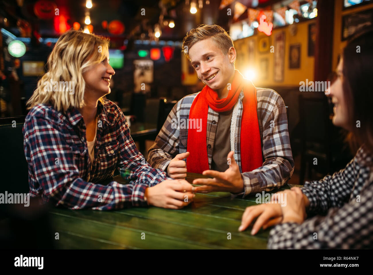 Teenagers sitting at the table in sports bar. Football fans, game tv broadcasting, young friends leisures in pub - Stock Image