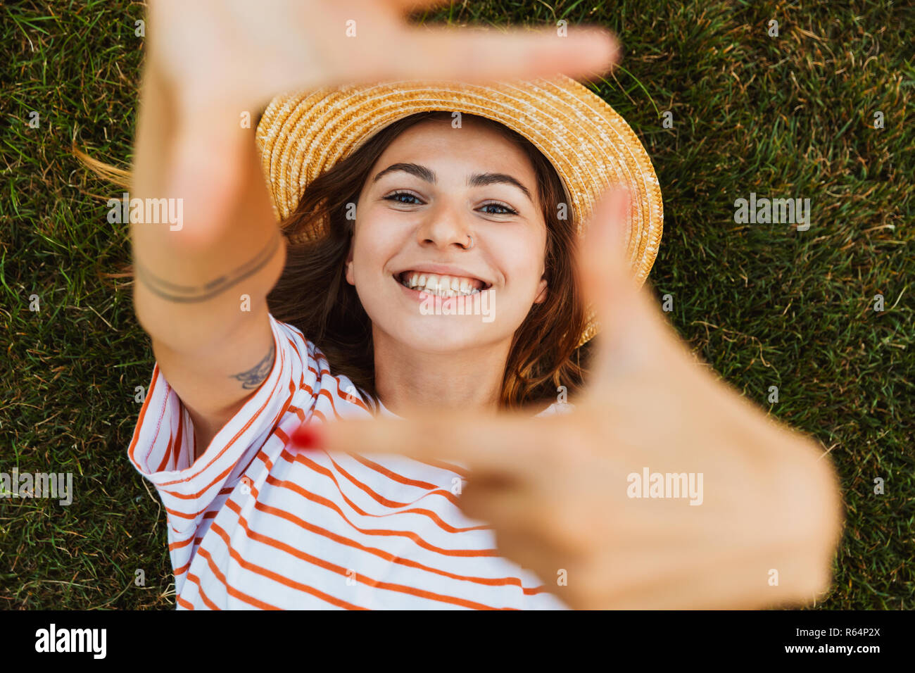 Top view of a cheerful young girl in summer hat laying on a grass, grimacing, outstretched hands - Stock Image