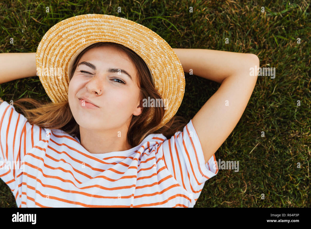 Top view of a funny young girl in summer hat laying on a grass, grimacing - Stock Image