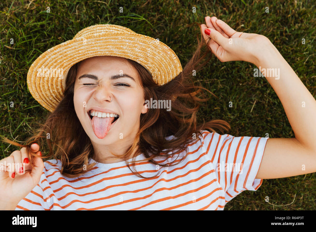 Top view of a lovely young girl in summer hat laying on a grass, grimacing, winking - Stock Image