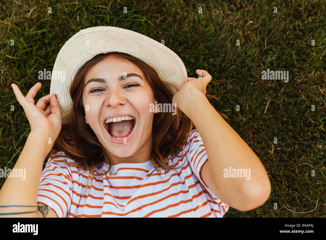 Top view of a joyful young girl in summer hat laying on a grass, grimacing - Stock Image