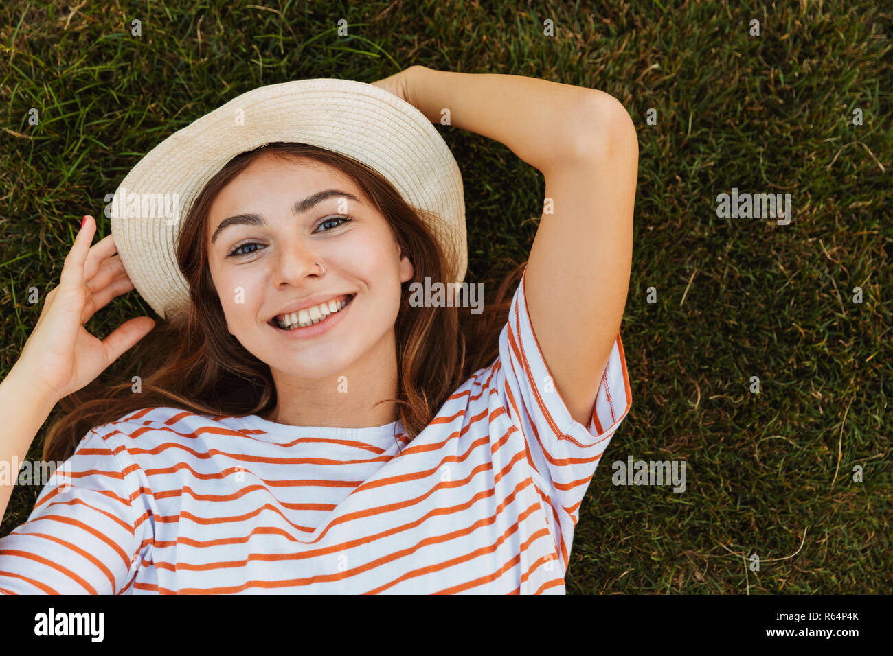 Top view of a delighted young girl in summer hat laying on a grass, grimacing - Stock Image