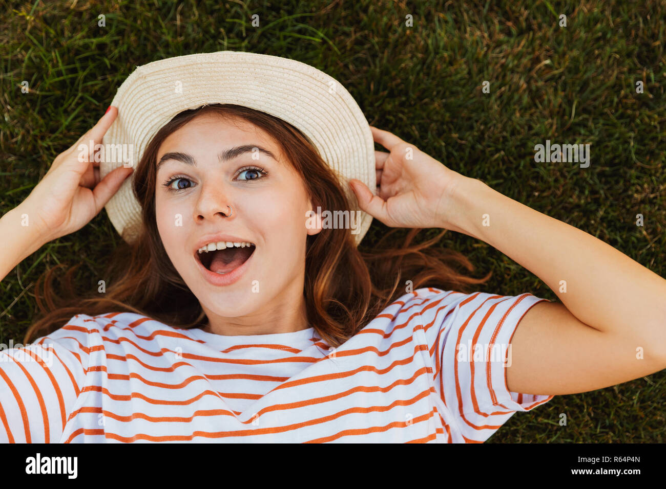 Top view of an excited young girl in summer hat laying on a grass, grimacing - Stock Image