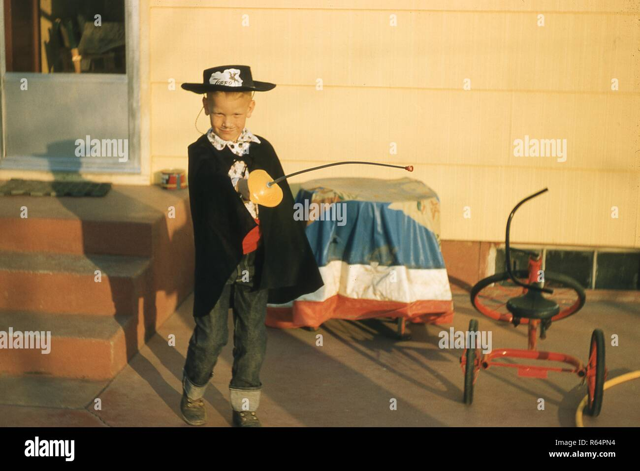 Portrait of a young boy dressed as the character Zorro, posing in the late afternoon sun outside his home in Ogden, Utah, October 31, 1958. () Stock Photo