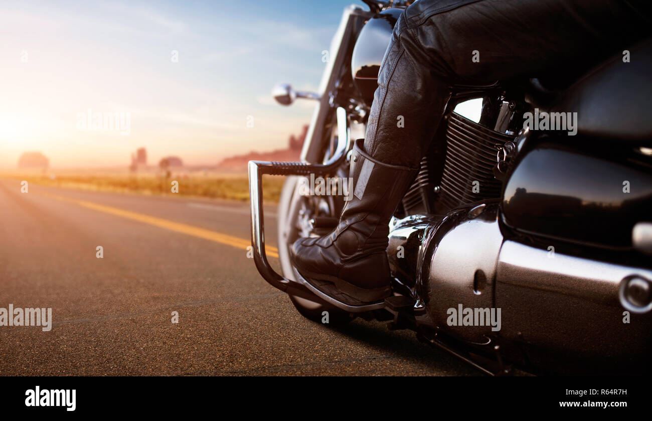 Biker riding on classical chopper, view from rear wheel. Vintage bike rider on motorcycle, road adventure in desert valley on sunset, freedom lifestyl - Stock Image
