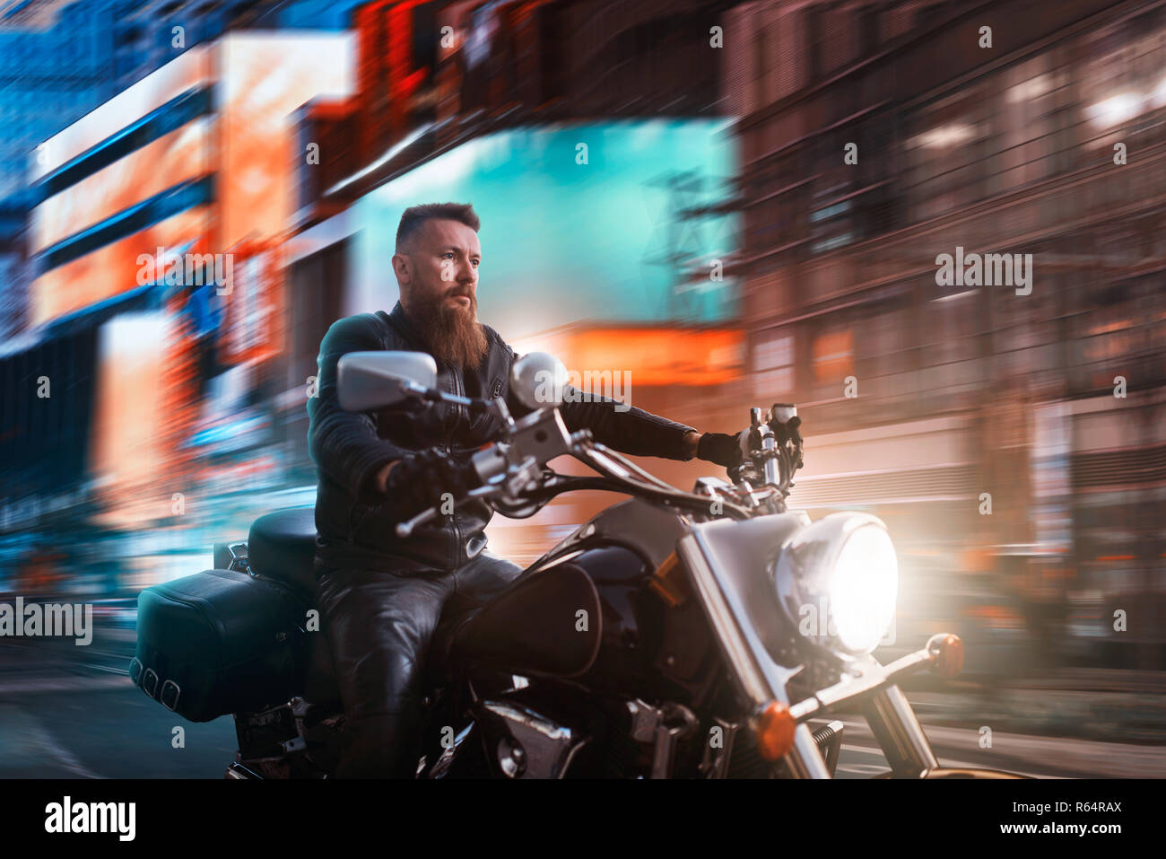 Biker riding on chopper through the night city, blured cityscape and advertising with neon lights on background. Vintage bike, rider on motorcycle, as - Stock Image
