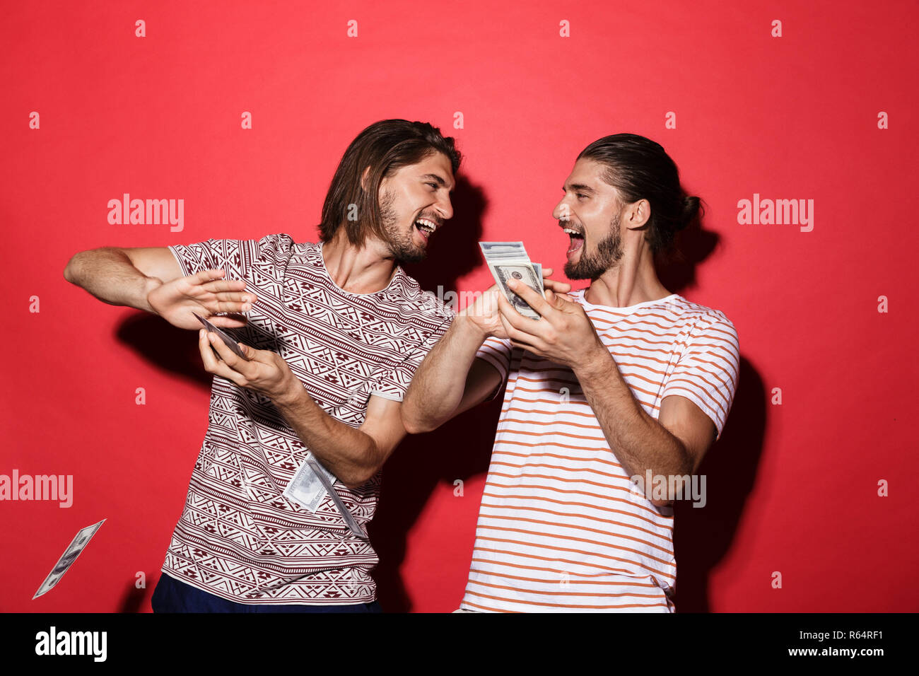Portrait of a two young cheerful twin brothers isolated over red background, throwing out money banknotes - Stock Image