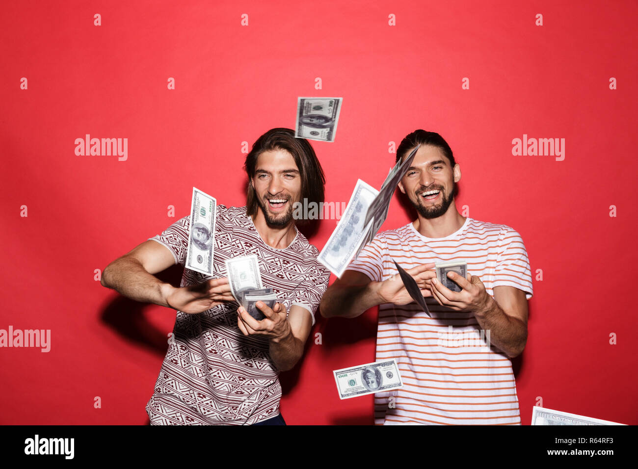 Portrait of a two young excited twin brothers isolated over red background, throwing out money banknotes - Stock Image
