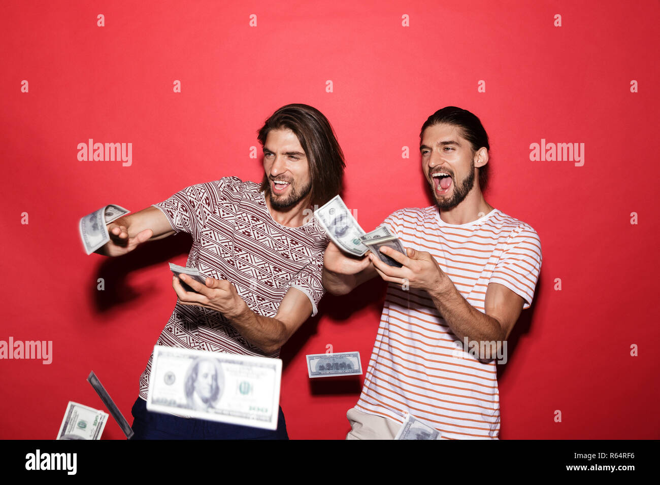 Portrait of a two young joyful twin brothers isolated over red background, throwing out money banknotes - Stock Image