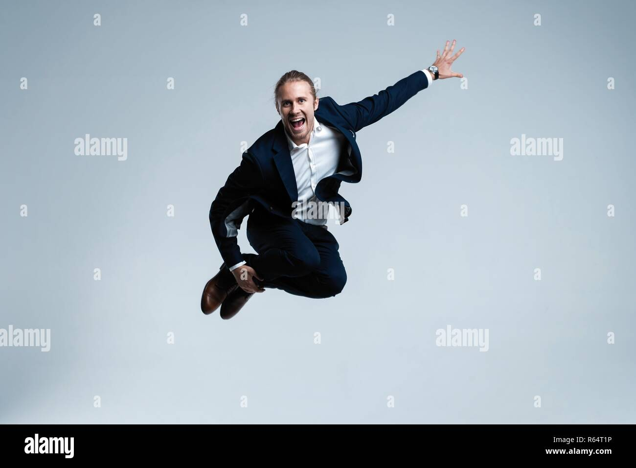 Young successful businessman in suit rejoicing, jumping over white background. Stock Photo