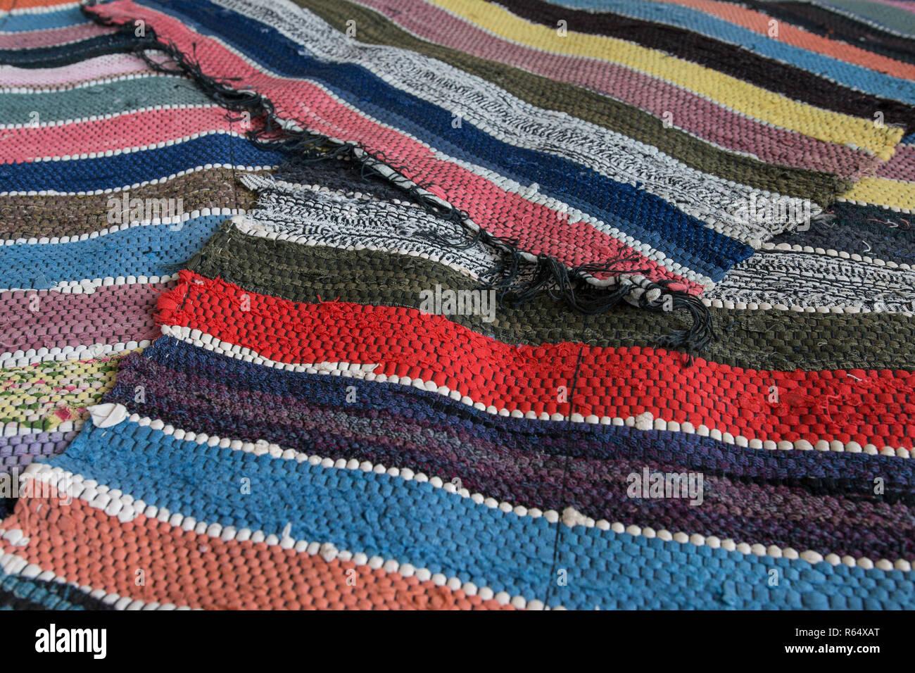 Traditional rustic striped multi-colored rug. Bright textile. Village eco concept. Selective focus - Stock Image