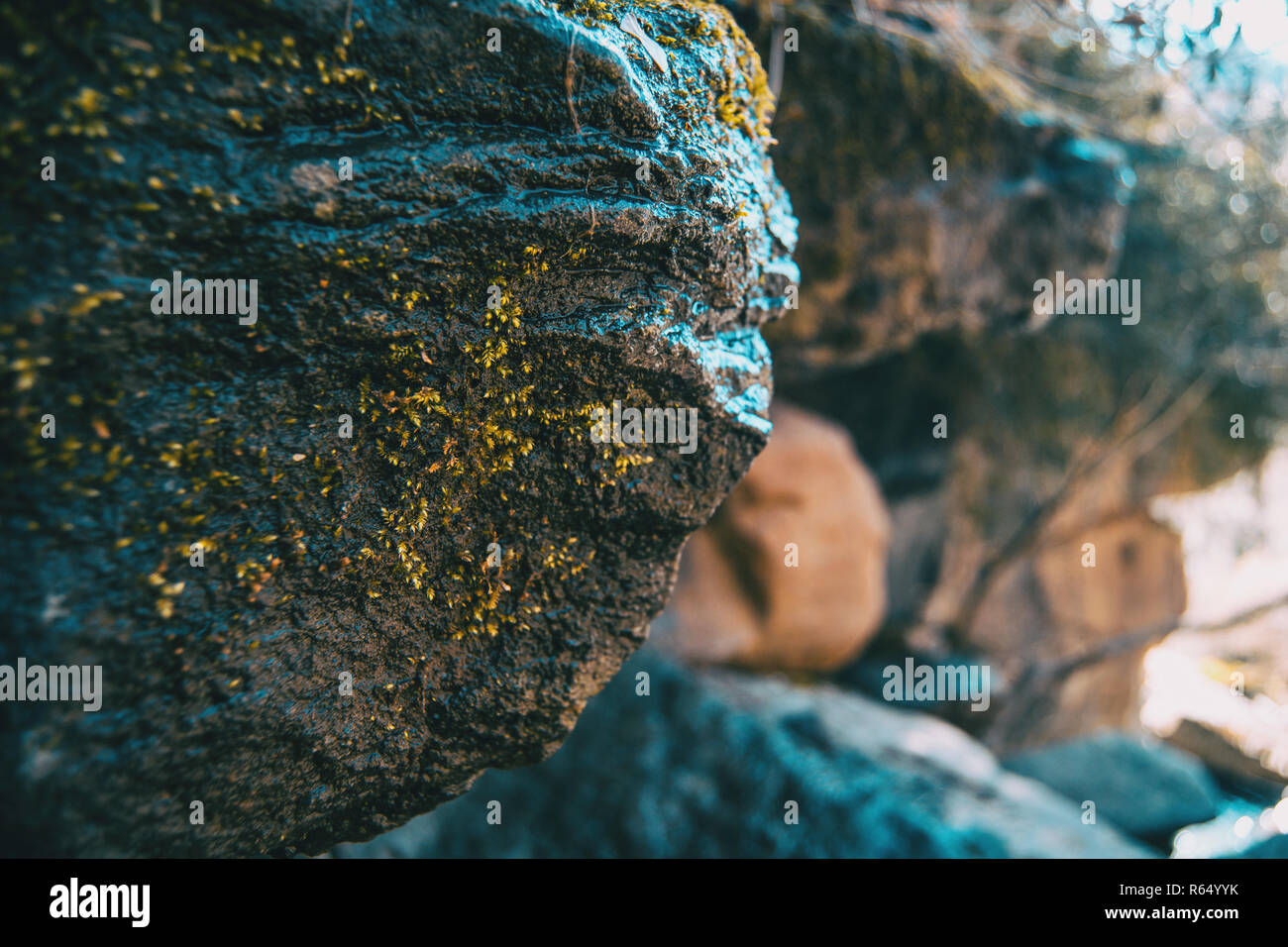 A big stone tilted with a bit of moss and more unfocused stones in the background - Stock Image