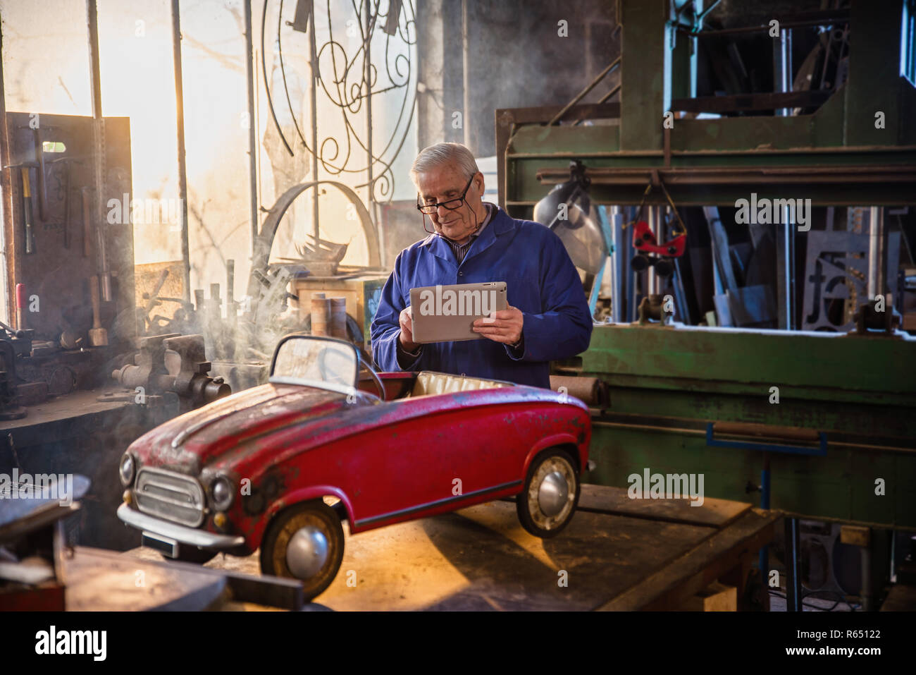 Senior man in his workshop repairing an old fashioned pedal car  Stock Photo
