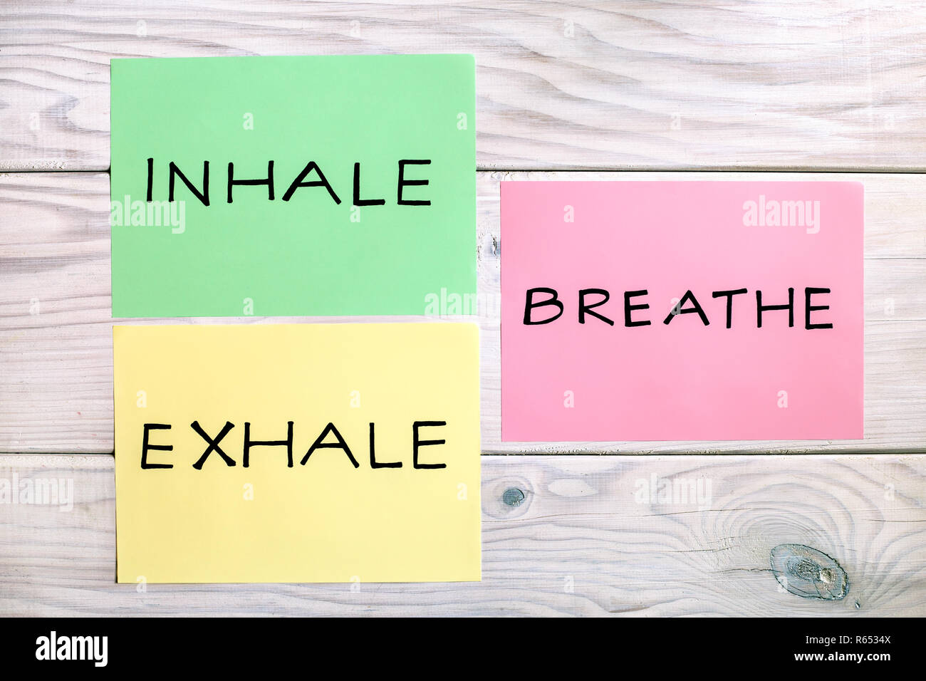 Words inhale,exhale and breath on wooden table. - Stock Image