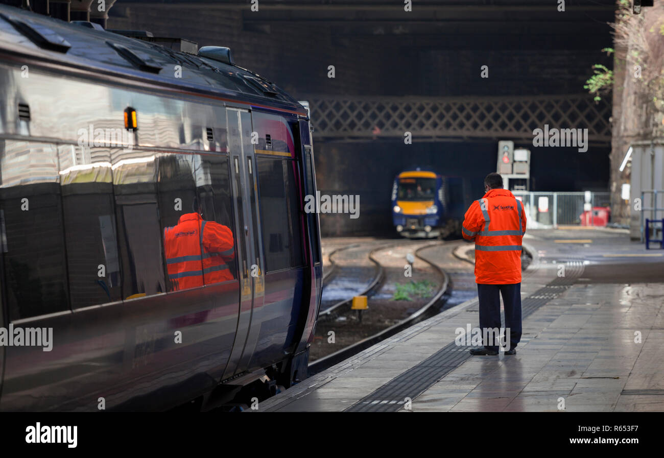 The driver of a Scotrail class 170 turbostar train at Glasgow Queen street, about to board his train as another arrives at the station. - Stock Image